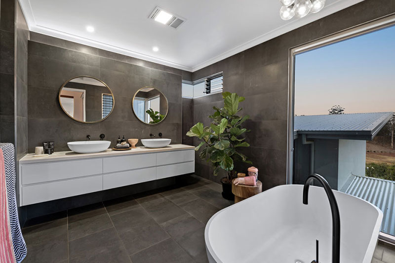 bathroom with three cabinet sinks