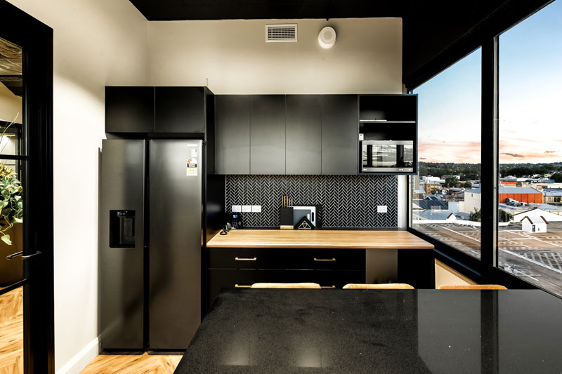 black colored refrigerator and kitchen cabinets