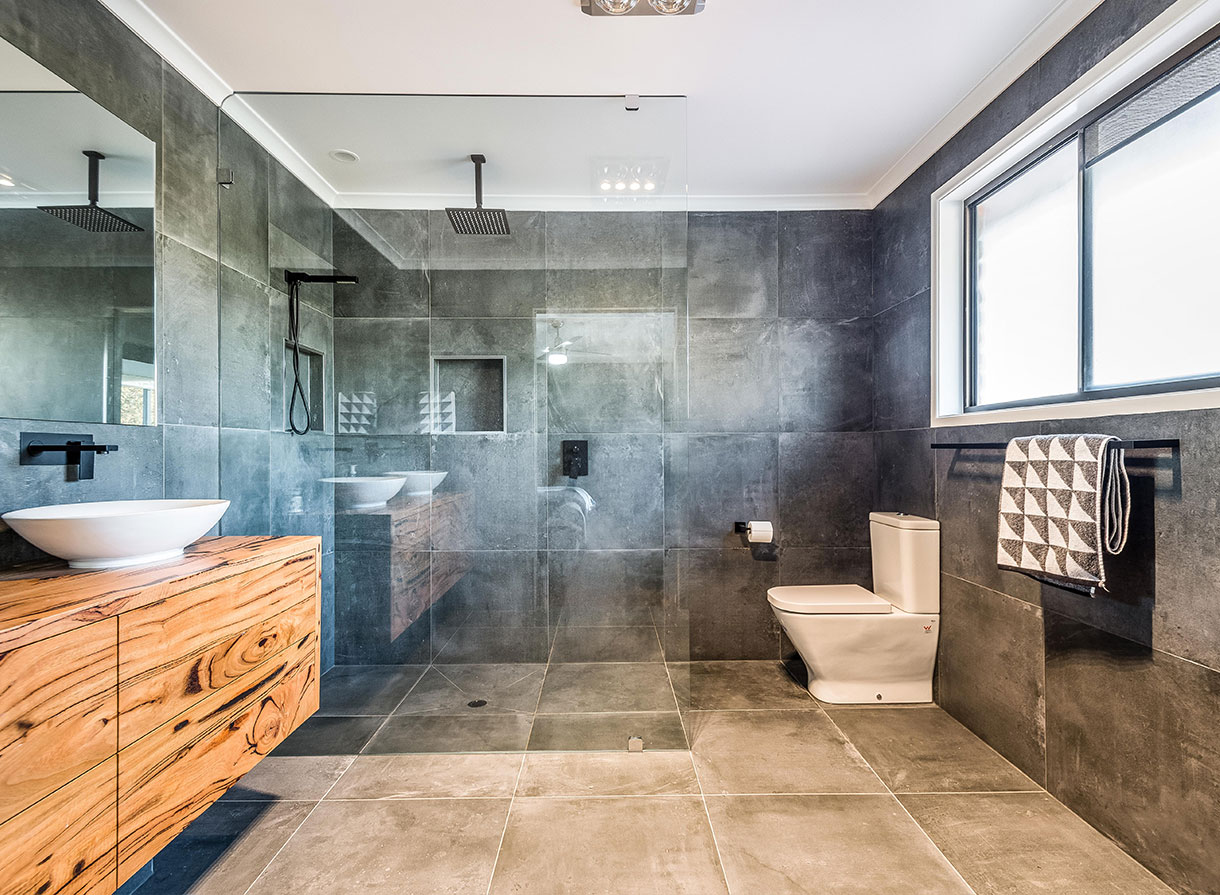 modern gray tiled bathroom with wooden style cabinet