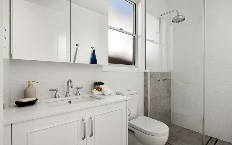 white themed bathroom cabinets and shower area