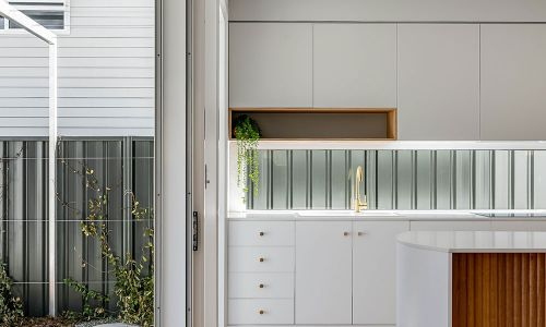 large exit sliding door and white kitchen cabinets