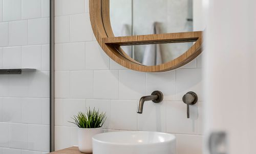 bathroom sink and circular mirror