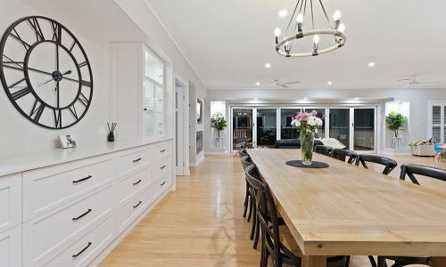 dining area with clock and white colored cabinets