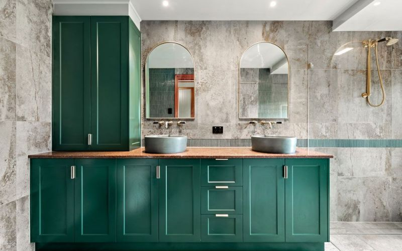 2 bathroom sink and mirror with green cabinets